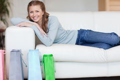 Woman relaxing on the sofa next to her shopping Stock Image