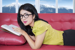Woman relaxing on sofa while reading book Stock Photo