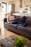 Woman Relaxing On Sofa Reading Newspaper In Modern Apartment Stock Photo