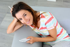 Woman relaxing in sofa with smartphone in hands Royalty Free Stock Photos