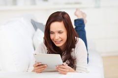 Woman relaxing on a sofa with a tablet Royalty Free Stock Photography