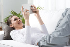 Woman relaxing on sofa with tablet Royalty Free Stock Photo