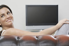 Woman Relaxing On Sofa With TV In Background Stock Photos