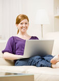 Woman relaxing on sofa typing on laptop Royalty Free Stock Image