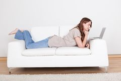 Woman relaxing on sofa using laptop Stock Photos