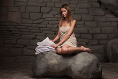 Woman relaxing in spa resort. Portrait of beautiful woman sitting in towel relaxing in spa resort against stone wall background stock photos
