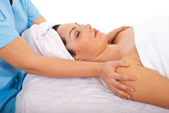 Woman relaxing at spa retreat. Beauty woman relaxing on spa massage table while a beautician woman holding hands on her shoulders Stock Photo