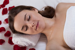 Woman relaxing at spa with rose petals Royalty Free Stock Image