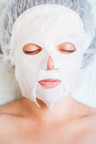 Woman relaxing in spa salon applying white face mask Royalty Free Stock Photo