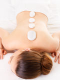 Woman relaxing in spa salon having therapy with stones. Adult woman relaxing in spa salon having therapy with hot stones on backbone Stock Image