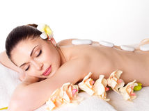Woman relaxing in spa salon with hot stones. Adult beautiful woman relaxing in spa salon with hot stones on back Stock Photos