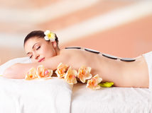 Woman relaxing in spa salon with hot stones. Adult beautiful woman relaxing in spa salon with hot stones on back Royalty Free Stock Images