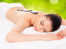 Woman relaxing in spa salon with hot stones Royalty Free Stock Photo