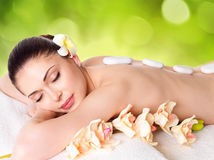 Woman relaxing in spa salon with hot stones Stock Photo