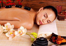 Woman relaxing in spa salon with hot stones on back Royalty Free Stock Image