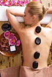 Woman relaxing in spa salon with hot stones on body. Stock Images