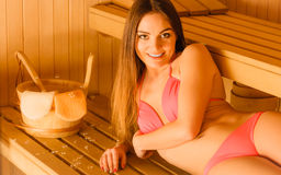 Woman relaxing in spa sauna with bucket. Wellbeing Royalty Free Stock Photo