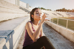 Woman relaxing after sports and drinking water Royalty Free Stock Photography