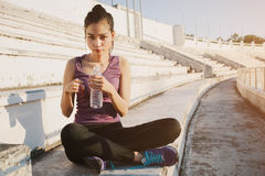Woman relaxing after sports and drinking water Royalty Free Stock Photo