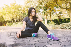 Woman relaxing after sports. Hipster student in the city park Royalty Free Stock Image
