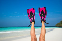 Woman relaxing on summer beach vacation holidays lying in sand. Flippers in legs. Diver fins Royalty Free Stock Photography