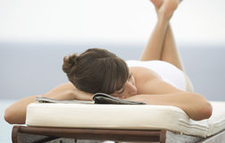 A woman relaxing on a sun lounger Stock Photo