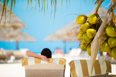 Woman relaxing on sun lounger under a coconut tree Stock Photos