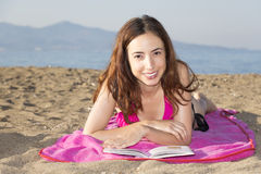 Woman relaxing and sunbathing on the beach Stock Photo