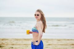 Woman relaxing and sunbathing on beach, drinking delicious fruit juice Stock Images
