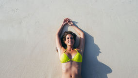 Woman relaxing and sunbathing at the beach on summer travel stock photos