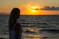 Woman relaxing at sunset sea Royalty Free Stock Image