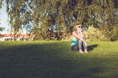 Woman relaxing in the sunshine on a green lawn. Sitting on the grass wearing sunglasses and staring off into the distance lost in thought Royalty Free Stock Images