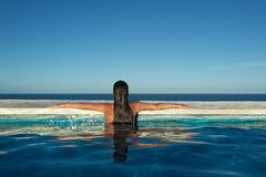 Woman relaxing in a swimming pool Royalty Free Stock Photography