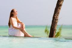 Woman relaxing by swimming pool Stock Photo
