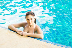 Woman relaxing in a swimming pool Stock Photos