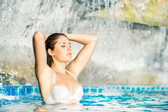 Woman relaxing in a swimming pool Royalty Free Stock Image