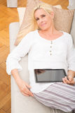 Woman relaxing with tablet on the sofa Stock Image