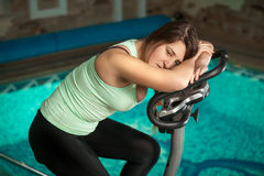Woman relaxing after training on exercise bike Stock Photography