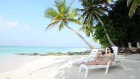 Woman is relaxing on the tropical beach stock video