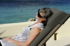 Woman relaxing on a tropical beach. Woman on vacation relaxing at a resort beach stock photography