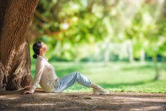 Woman relaxing under big tree. Young woman relaxing under big tree in the park outdoors Stock Images