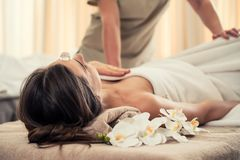 Woman relaxing under the therapeutic effect of a crystal placed. Young woman relaxing on massage bed under the positive therapeutic effect of a crystal placed on Stock Image