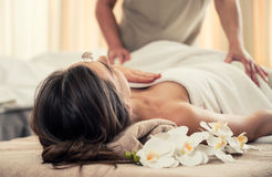Woman relaxing under the therapeutic effect of a crystal placed. Young women relaxing on massage bed under the positive therapeutic effect of a crystal placed on stock photo