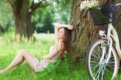 Woman relaxing under a tree next to a bicycle Stock Photo