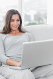 Woman relaxing and using her laptop Royalty Free Stock Photos