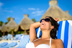 Woman on relaxing vacation at tropical resort beach sunbathing. Joyful woman at tropical resort caribbean beach resting on outdoor chaise lounge. Summertime Royalty Free Stock Images