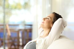 Woman relaxing on vacations in an apartment. Side view portrait of a happy woman relaxing sitting on a couch on vacations in an apartment on the beach Stock Photography