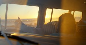 Woman relaxing in the van 4k. Woman relaxing in the van. Beautiful sunset in the background 4k stock footage