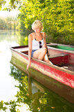 Woman relaxing on the vintage wooden boat. Thoughtful young blonde woman enjoying the sunny summer day on a vintage wooden boats on a lake in pure natural Stock Image