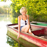 Woman relaxing on the vintage wooden boat. Thoughtful young blonde woman enjoying the sunny summer day on a vintage wooden boats on a lake in pure natural Stock Photography